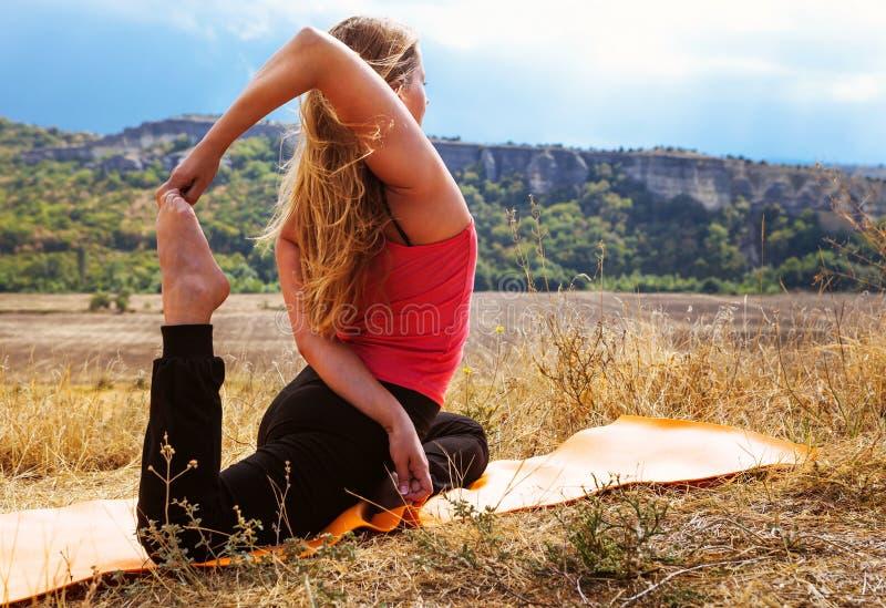 De jonge vrouw maakt flexibele yogaoefening royalty-vrije stock foto's