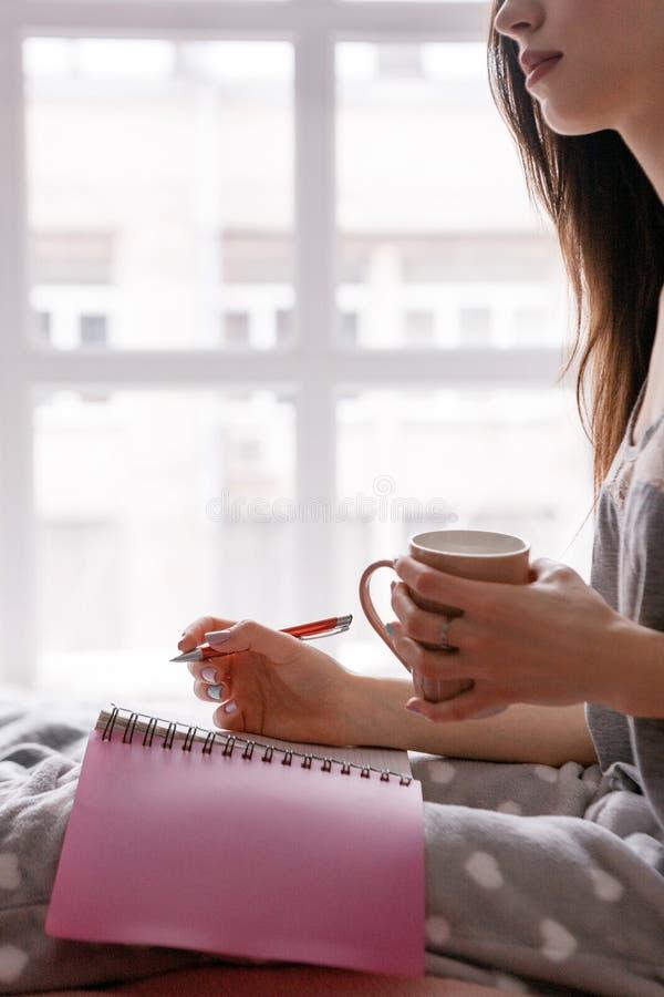 De jonge vrouw maakt nota's in het schrijven van boek stock foto