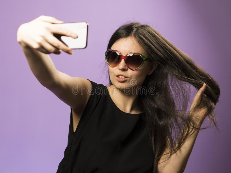 De jonge Vrouw maakt Selfie in Zonnebril op Purpere Achtergrond Foto in Googles op Recentste Iphone X stock afbeelding