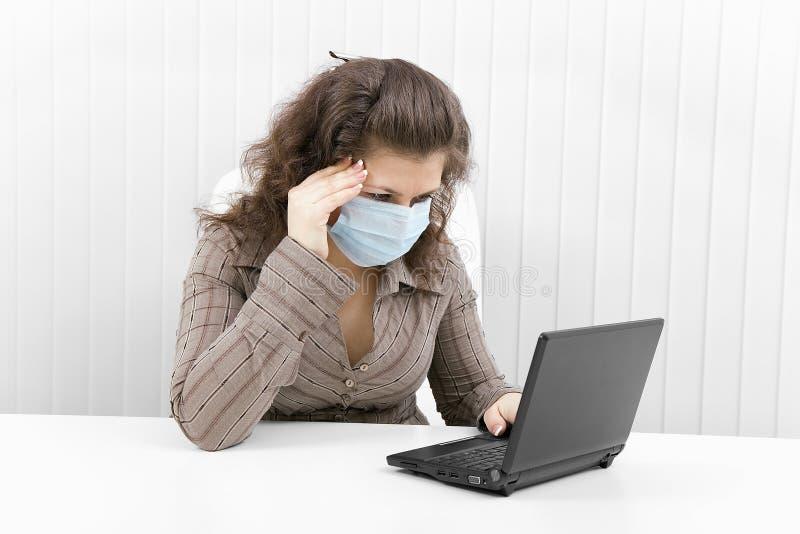 De jonge vrouw in medisch masker met laptop stock fotografie