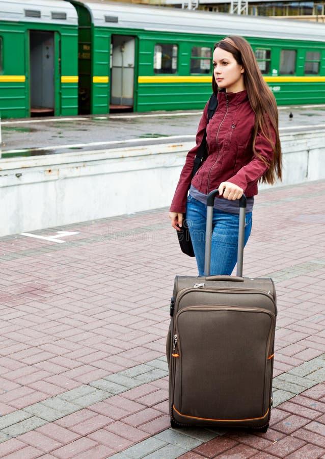 De jonge vrouw met bagage wacht een trein royalty-vrije stock afbeelding