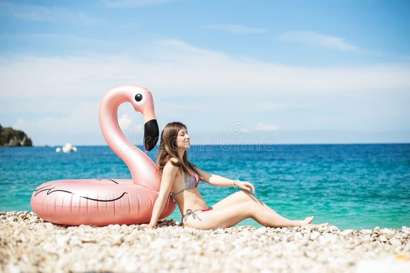 de jonge vrouw met bikinizitting dicht bij reus blies