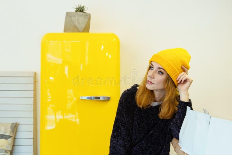 De jonge vrouw met blond haar in een gele hoed zit in een koffie dichtbij aan gele koelkast royalty-vrije stock fotografie
