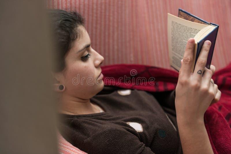 De jonge vrouw met bruin haar leest stil een boek liggend op de verpakte bank in een rode deken stock fotografie