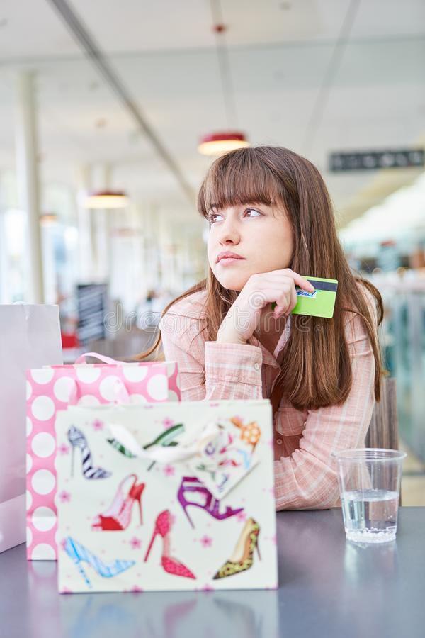 De jonge vrouw met creditcard is bored stock afbeelding