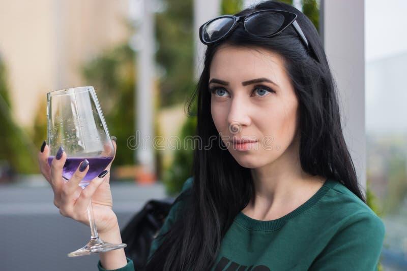 De jonge vrouw met een glas van violette cocktail zit op het de zomerterras van het restaurant royalty-vrije stock foto