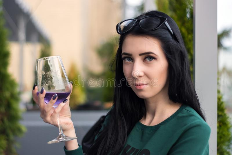 De jonge vrouw met een glas van violette cocktail zit op het de zomerterras van het restaurant royalty-vrije stock afbeelding