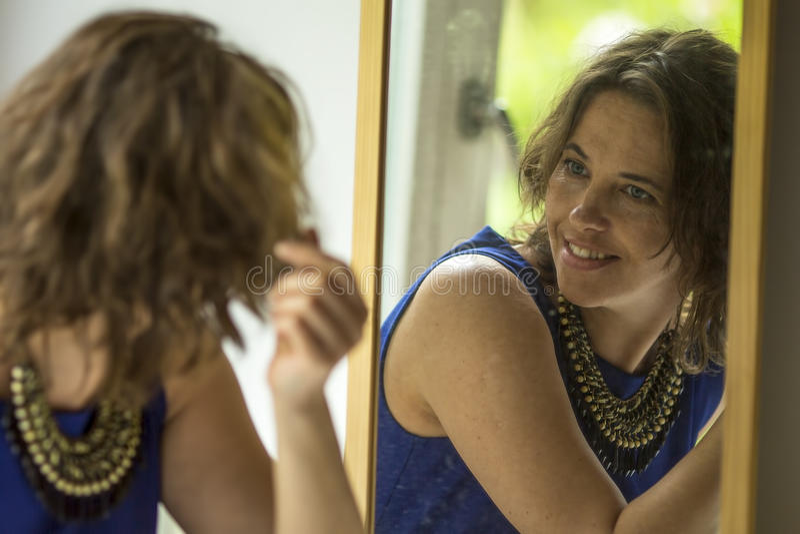 De jonge vrouw met een glimlach kijkt in de spiegel gelukkig royalty-vrije stock foto's