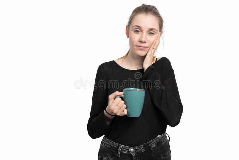 De jonge vrouw met een koffiekop in haar hand is vermoeid royalty-vrije stock fotografie