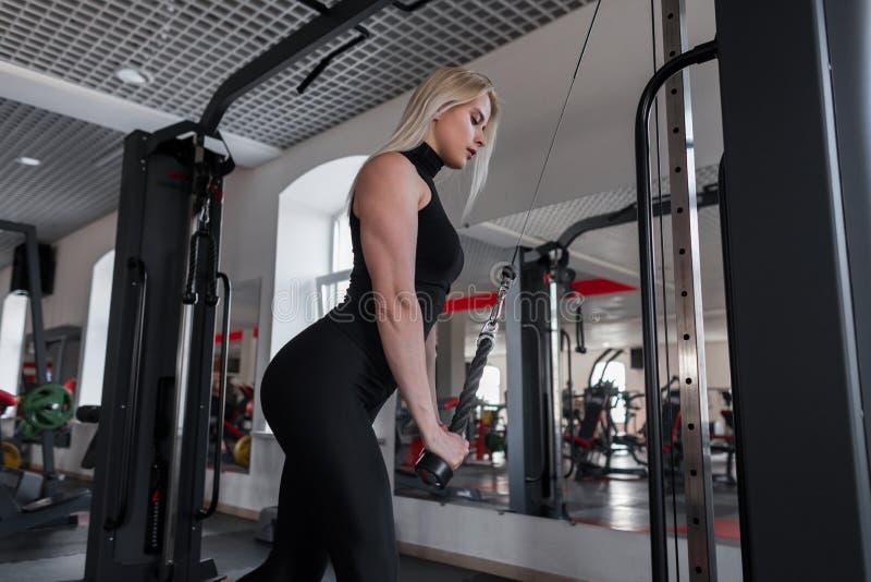 De jonge vrouw met een mooi lichaam in sportkleding speelt sporten in een gymnastiek Meisje bij training in geschiktheidsstudio royalty-vrije stock afbeelding