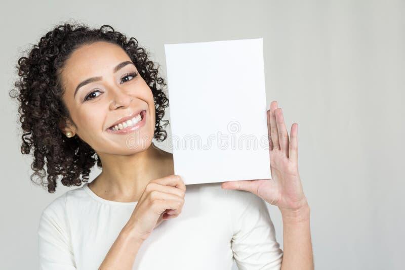 De jonge vrouw met een mooie glimlach houdt een lege raad royalty-vrije stock fotografie