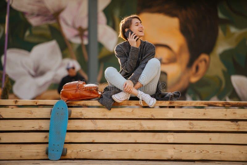 De jonge vrouw met een skateboard rust op een 2 stadiumbank, telefonerend stock afbeelding