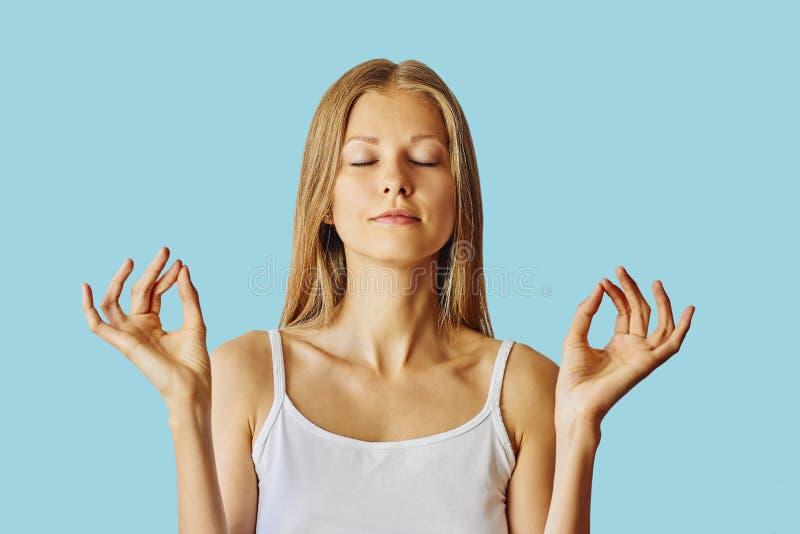 De jonge vrouw met gesloten ogen en dient lotusbloemgebaar in Meditatie, saldo en vrede van meningsconcept Over blauw stock foto's
