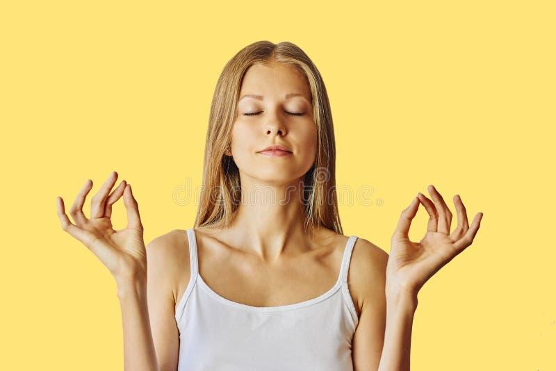 De jonge vrouw met gesloten ogen en dient lotusbloemgebaar in Meditatie, saldo en vrede van meningsconcept over geel stock foto's