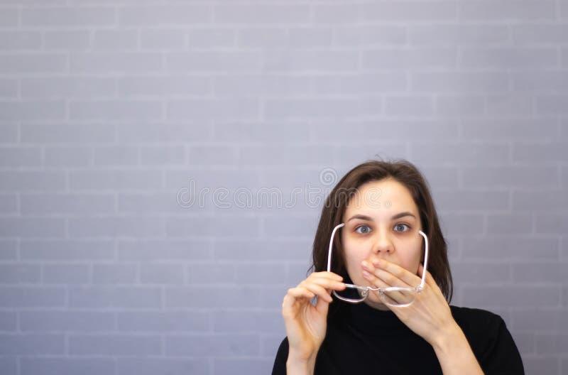 De jonge vrouw met glazen in haar handen behandelde haar mond stock foto's