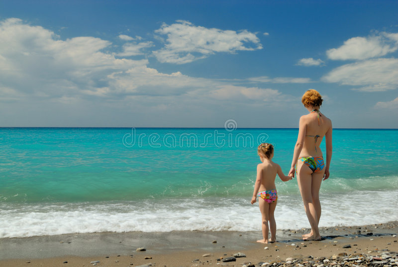 De jonge vrouw met haar kind kijkt op het strand royalty-vrije stock afbeelding
