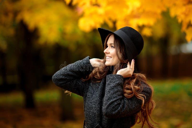 De jonge vrouw met de herfst verlaat en daling ter beschikking gele esdoorngeep stock fotografie