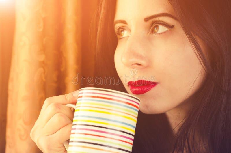 De jonge vrouw met het denken gezicht kijkt aan het venster met een kop thee in handen royalty-vrije stock afbeeldingen