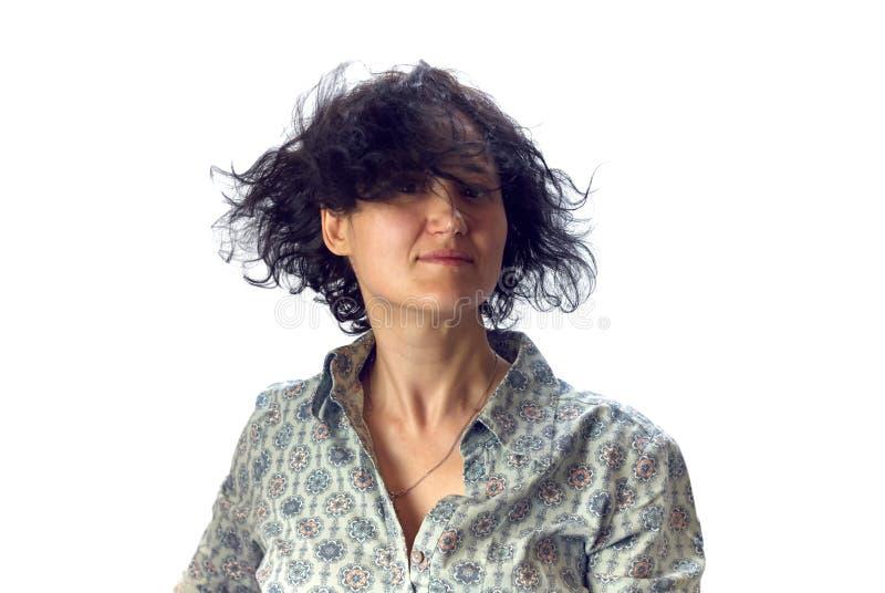 De jonge vrouw met het zwarte krullende golven in het windhaar bekijkt de camera stock afbeelding