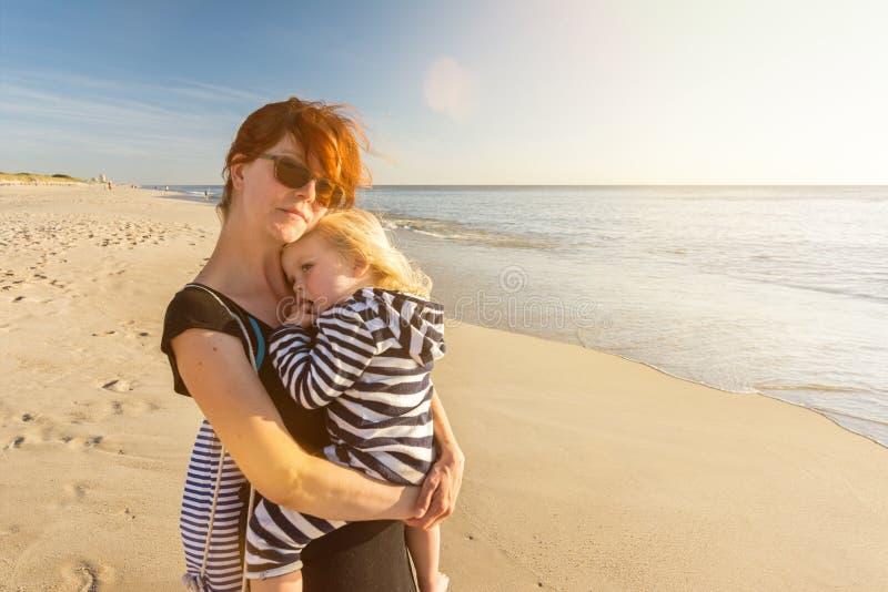 De jonge vrouw met kind in haar wapens ontspant op het strand en geniet van de zonsondergang stock afbeeldingen