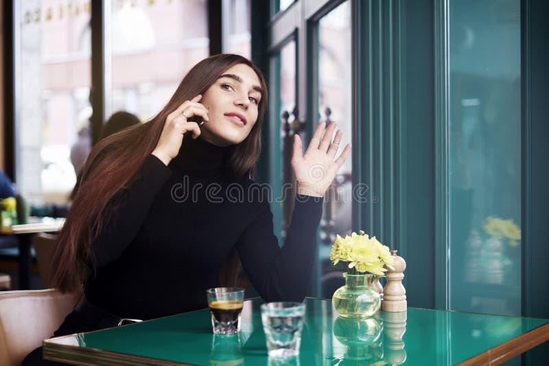 De jonge vrouw met lang haar geeft hallo-vijf aan iemand, die koffie drinken die rust in koffie hebben dichtbij venster royalty-vrije stock afbeeldingen