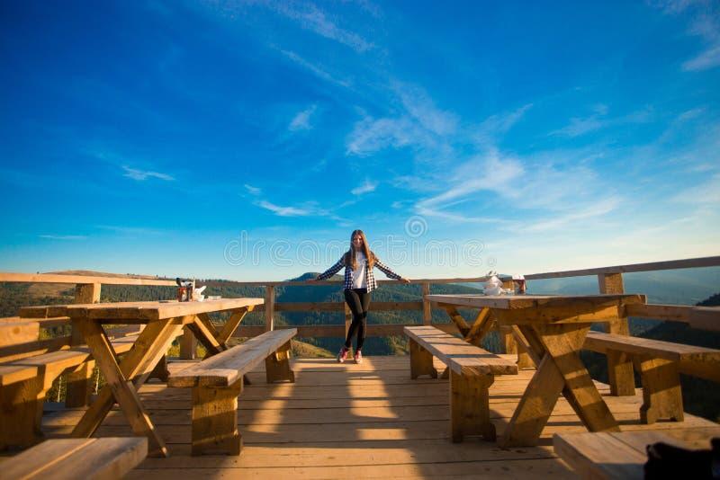 De jonge vrouw met lang haar heeft rust in openluchtkoffie bovenop bergen en geniet van mening stock afbeeldingen