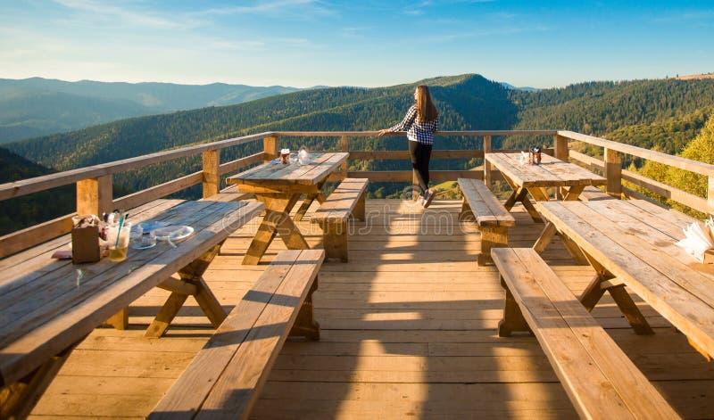 De jonge vrouw met lang haar heeft rust in openluchtkoffie bovenop bergen en geniet van mening royalty-vrije stock fotografie
