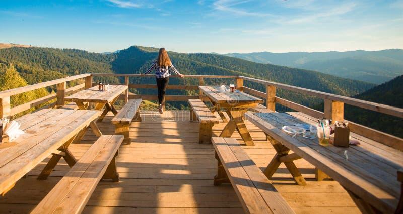 De jonge vrouw met lang haar heeft rust in openluchtkoffie bovenop bergen en geniet van mening royalty-vrije stock afbeelding