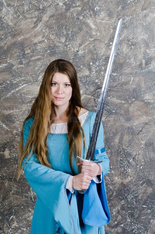 De jonge vrouw met lang haar stelt met zwaard royalty-vrije stock afbeelding