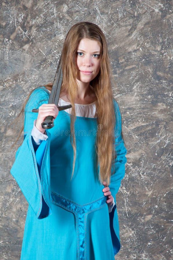 De jonge vrouw met lang haar stelt met zwaard stock afbeeldingen