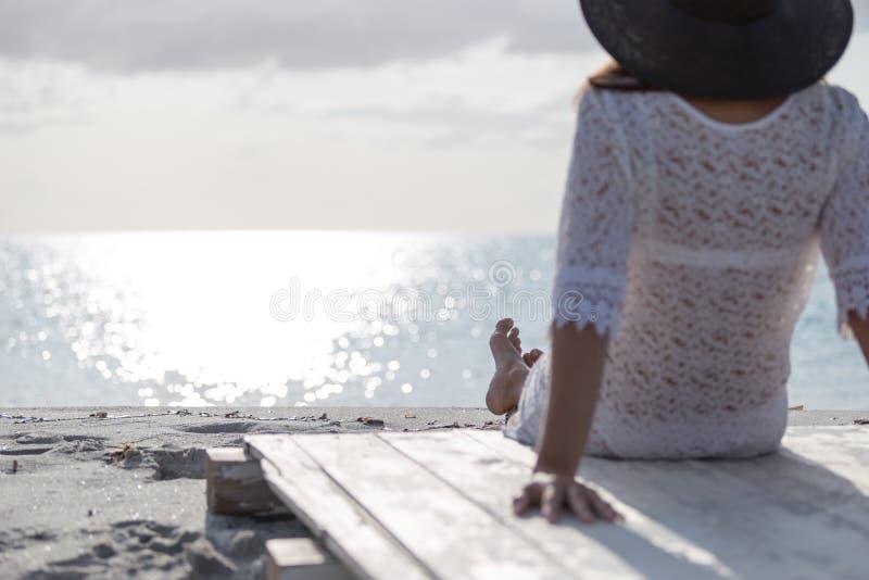 De jonge vrouw met lang haar van achter zitting door het overzees bekijkt de horizon bij dageraad in de wind, gekleed in een witt stock afbeeldingen