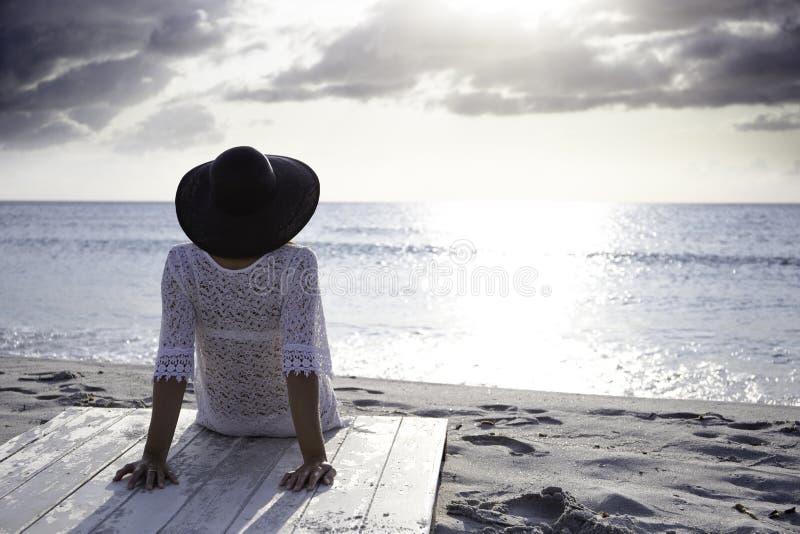 De jonge vrouw met lang haar van achter zitting door het overzees bekijkt de horizon bij dageraad in de wind, gekleed in een witt royalty-vrije stock foto's