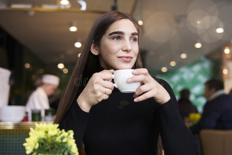 De jonge vrouw met lang haar voelt eenzaam, dromen, die koffie in handen drinken die rust in koffie hebben dichtbij venster royalty-vrije stock fotografie
