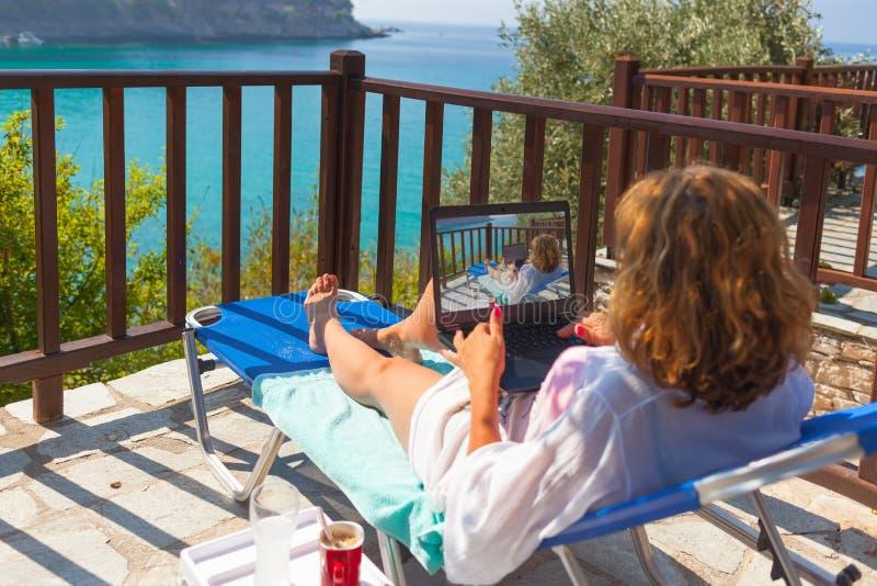 De jonge vrouw met laptop in een ligstoel geniet van zonlicht royalty-vrije stock afbeeldingen