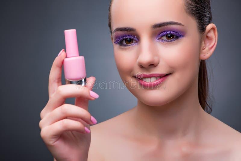 De jonge vrouw met lippenstift in beautconcept royalty-vrije stock afbeeldingen