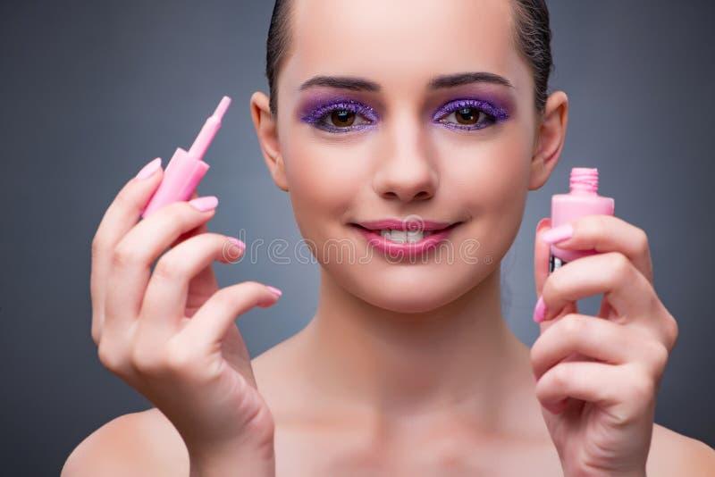 De jonge vrouw met lippenstift in beautconcept stock afbeeldingen