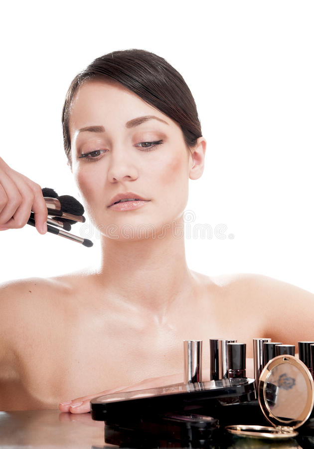 De jonge vrouw met make-up borstelt dichtbij het gezicht. stock afbeelding