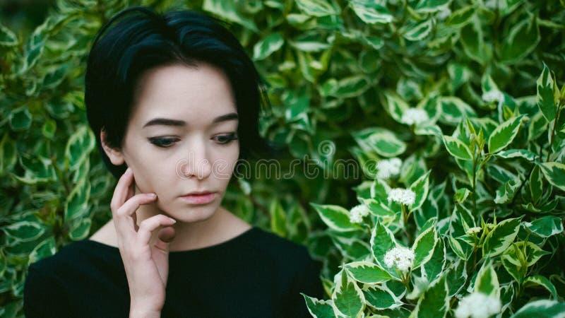 De jonge vrouw met mooie voeten kleedde zich in zwarte kleding, tegen een achtergrond van stedelijke landschappenstruik stock afbeeldingen