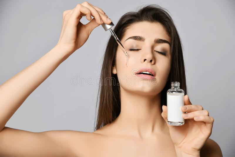De jonge vrouw met ogen sloot met genoegen van vernieuwingsdalingen van een glashelder schoonheidsmiddel voor huid van pipet op h royalty-vrije stock afbeelding