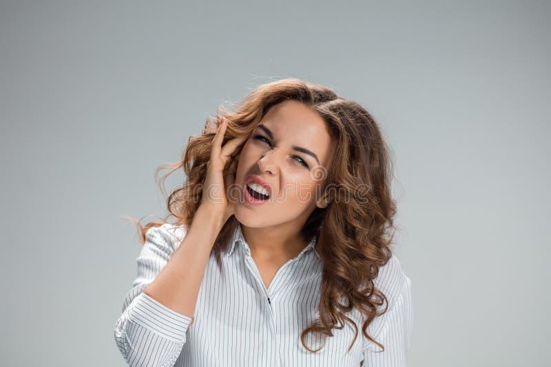 De jonge vrouw met oorpijn over grijs royalty-vrije stock foto