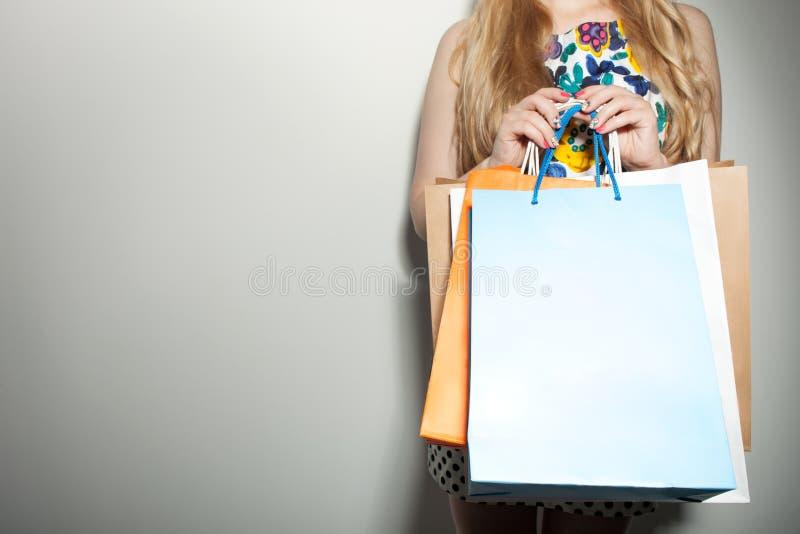 De jonge vrouw met pakketten is het gaande winkelen stock foto