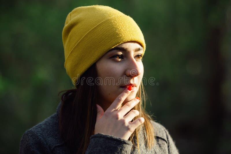 De jonge vrouw met rode vingernagels draagt een geel GLB en raakt haar lippen stock foto