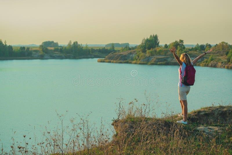 De jonge vrouw met roze rugzak staat op de blauwe achtergrond van krijtsteengroeven dicht in zonsondergangtijd op royalty-vrije stock foto