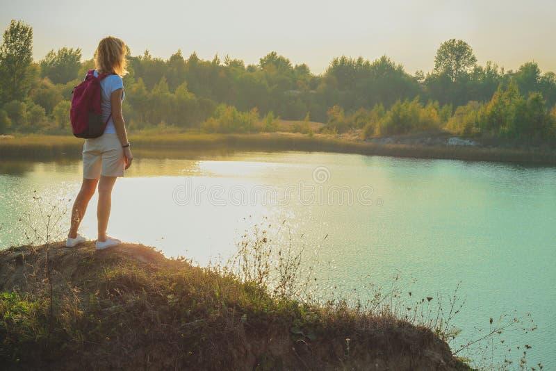 De jonge vrouw met roze rugzak staat op de blauwe achtergrond van krijtsteengroeven dicht in zonsondergangtijd op stock fotografie