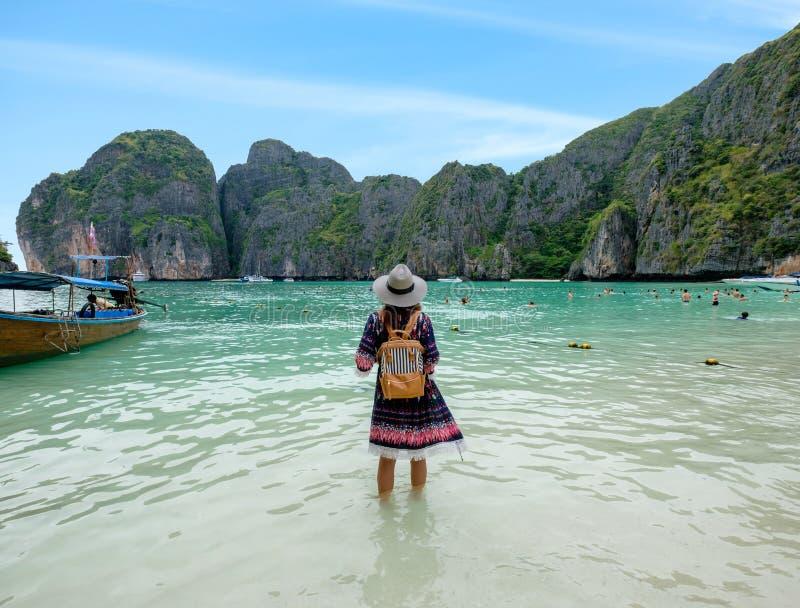 De jonge vrouw met rugzak geniet van op kust in maya baai stock afbeelding