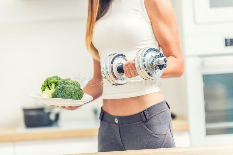 De jonge vrouw met sporten komt in de domoren van de keukenholding in haar handen en een plaat van broccoli voor stock foto