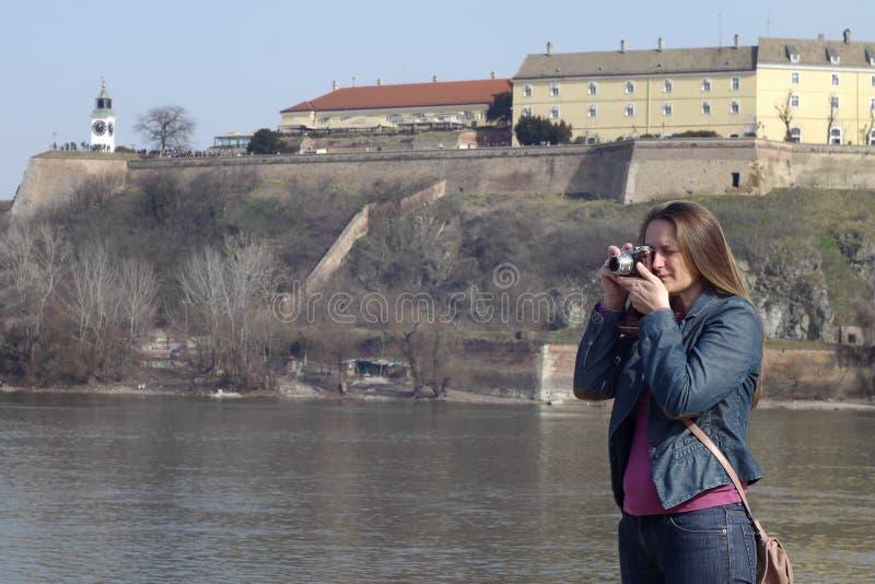 De jonge vrouw met uitstekende retro camera neemt foto's royalty-vrije stock afbeelding