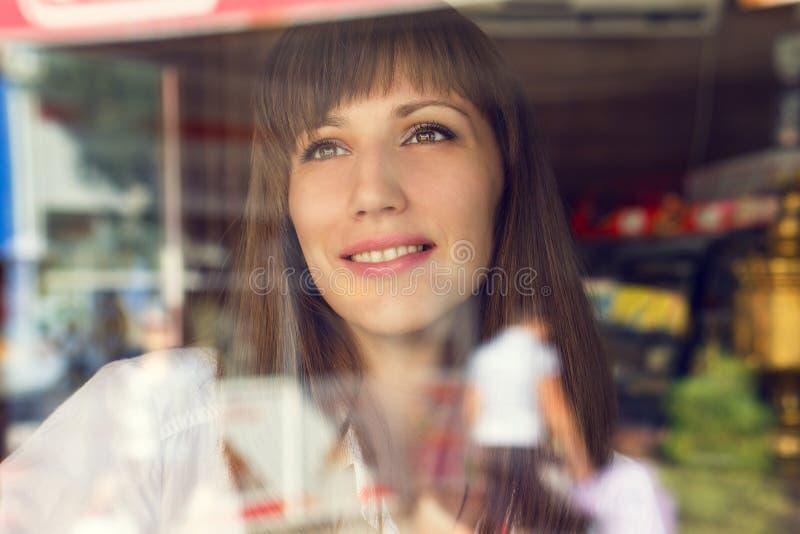 De jonge vrouw neemt een pret bij het restaurant Schoonheids volwassen meisje die en door venster glimlachen kijken stock fotografie