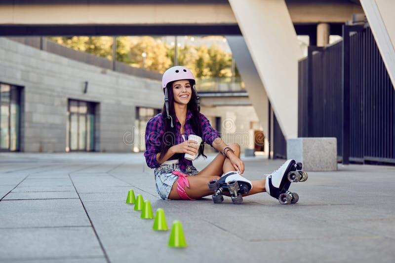 De jonge vrouw neemt een rust na het berijden van rolschaatsen en het drinken van koffie stock foto's