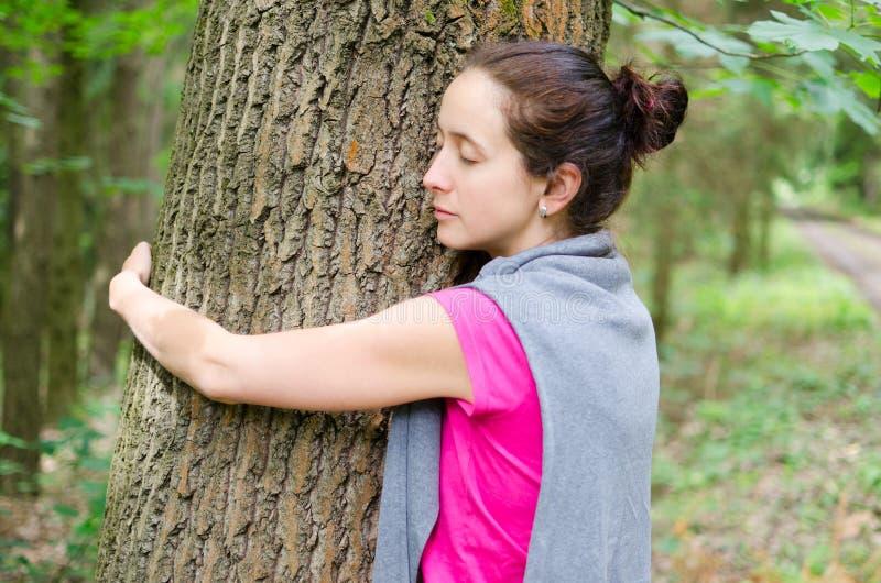De jonge vrouw omhelst boom royalty-vrije stock foto's